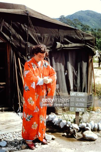 Outside her tent Lieutenant Slack of the 8063rd MASH adjust the sleeve of her brightly colored kimono South Korea January 1952