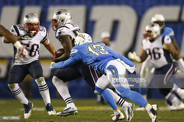 Outside linebacker Akeem Ayers of the New England Patriots intercepts the football and is tackled by intended receiver wide receiver Keenan Allen of...