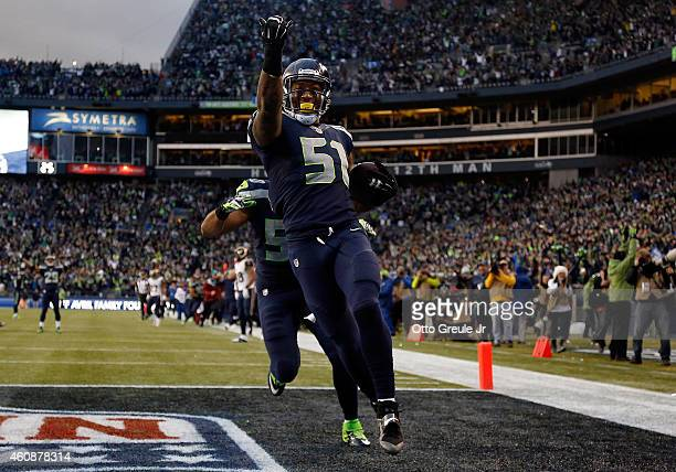 Outside linebacker Bruce Irvin of the Seattle Seahawks celebrates after running an interception back 49 yards for a touchdown during the fourth...