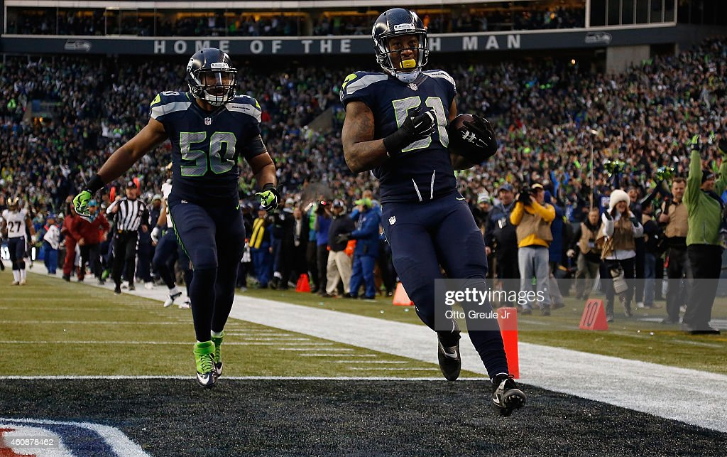 Outside linebacker Bruce Irvin #51 of the Seattle Seahawks celebrates with outside linebacker K.J. Wright #50 of the Seattle Seahawks after running an interception back 49 yards for a touchdown during the fourth quarter of the game against the St. Louis Rams at CenturyLink Field on December 28, 2014 in Seattle, Washington.