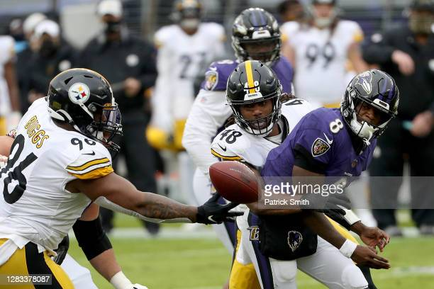 Outside linebacker Bud Dupree and defensive end Isaiah Buggs of the Pittsburgh Steelers pressure quarterback Lamar Jackson of the Baltimore Ravens in...