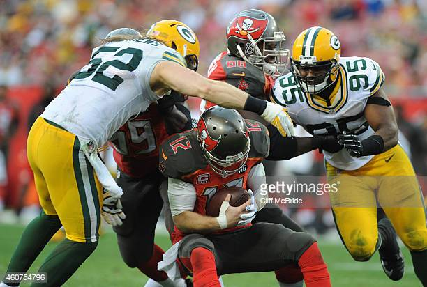 Outside linebacker Clay Matthews of the Green Bay Packers sacks quarterback Josh McCown of the Tampa Bay Buccaneers as teammate defensive end Datone...