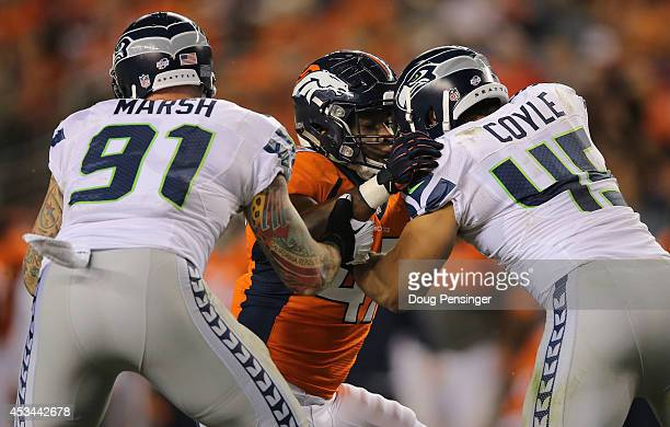 Outside linebacker Corey Nelson of the Denver Broncos rushes the line against defensive end Cassius Marsh and linebacker Brock Coyle of the Seattle...