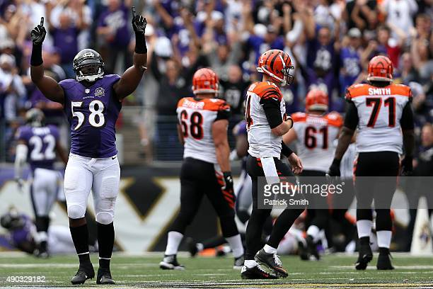Outside linebacker Elvis Dumervil of the Baltimore Ravens celebrates after forcing a fumble returned for a touchdown while quarterback Andy Dalton of...