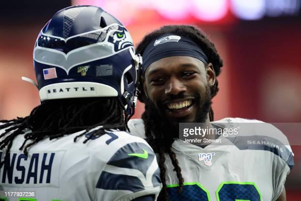 Outside linebacker Jadeveon Clowney of the Seattle Seahawks shares a laugh with defensive end Ezekiel Ansah during the NFL game against the Arizona...