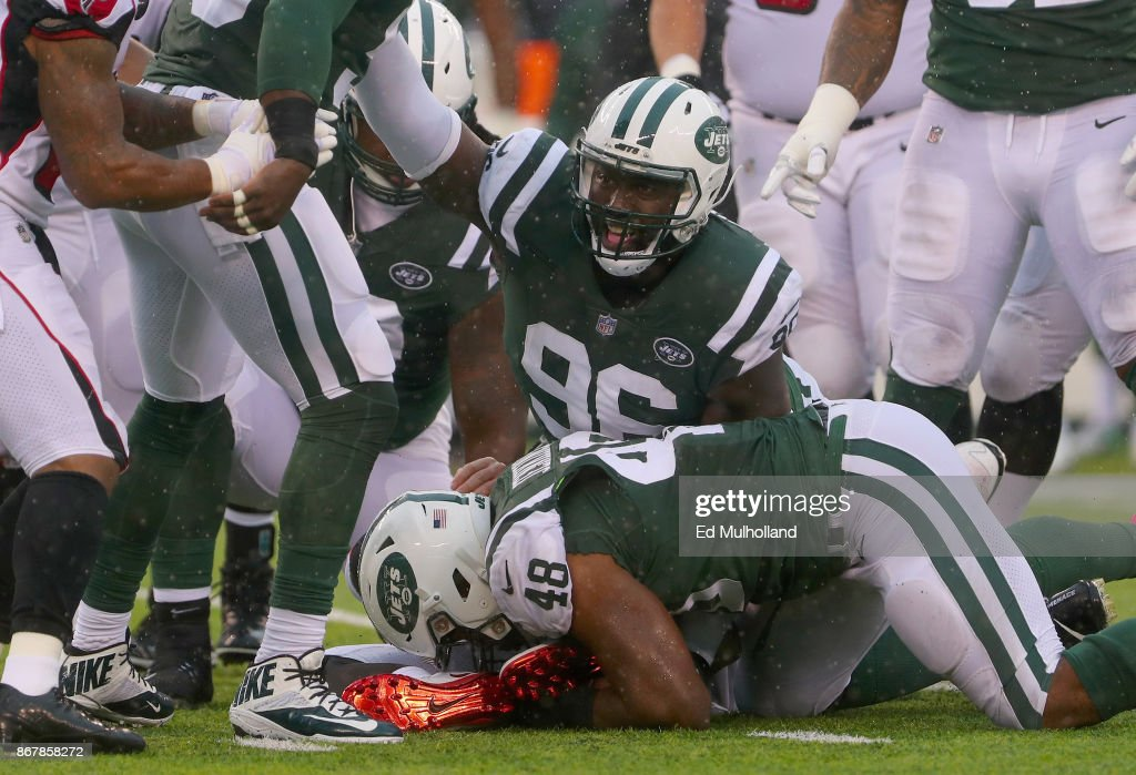 Outside linebacker Jordan Jenkins #48 of the New York Jets recovers the ball as teammate defensive end Muhammad Wilkerson #96 reacts against the Atlanta Falcons during the first quarter of the game at MetLife Stadium on October 29, 2017 in East Rutherford, New Jersey.