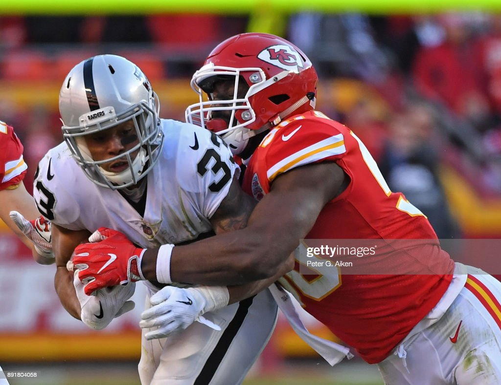 Outside linebacker Justin Houston #50 of the Kansas City Chiefs tackles running back DeAndre Washington #33 of the Oakland Raiders during the second half at Arrowhead Stadium on December 10, 2017 in Kansas City, Missouri.
