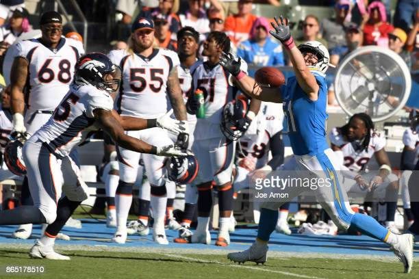 Outside linebacker Kyle Emanuel of the Los Angeles Chargers breaks up a pass to tight end Virgil Green of the Denver Broncos as the Denver Broncos...