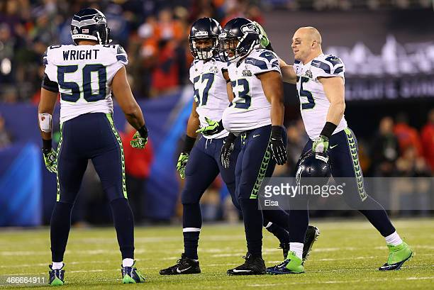 Outside linebacker Malcolm Smith of the Seattle Seahawks celebrates with outside linebacker Mike Morgan and outside linebacker KJ Wright during Super...