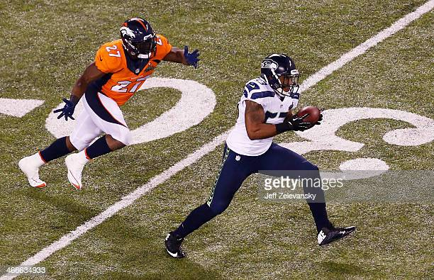 Outside linebacker Malcolm Smith of the Seattle Seahawks runs back an interception for 69 yards off quarterback Peyton Manning of the Denver Broncos...