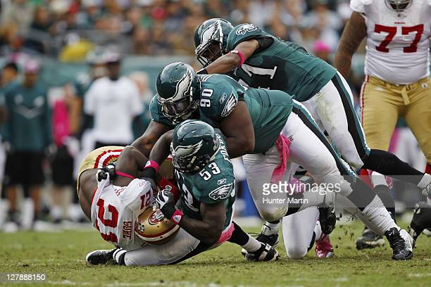 Outside linebacker Moise Fokou defensive tackle Antonio Dixon and strong safety Jarrad Page of the Philadelphia Eagles tackle running back Frank Gore...