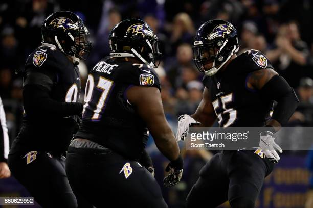 Outside Linebacker Terrell Suggs and nose tackle Michael Pierce of the Baltimore Ravens celebrate after a sack in the second quarter at MT Bank...