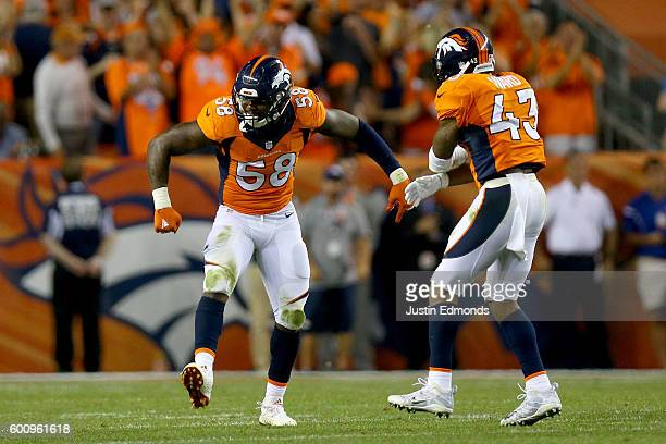 Outside linebacker Von Miller and strong safety TJ Ward of the Denver Broncos celebrate a Miller sack against the Carolina Panthers late in the...