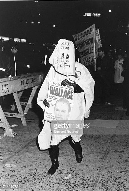 Outside Madison Square Garden during a George Wallace presidential campaign rally an unidentified man dressed in a white outfit and hood inscribed...
