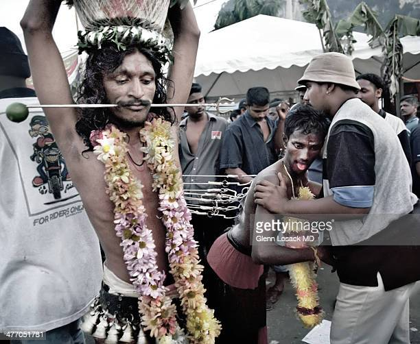CAVES outside of KUALA Devotee is pierced through his cheeks wearing garlands in a trance other man is pierced from his back with multiple hooks