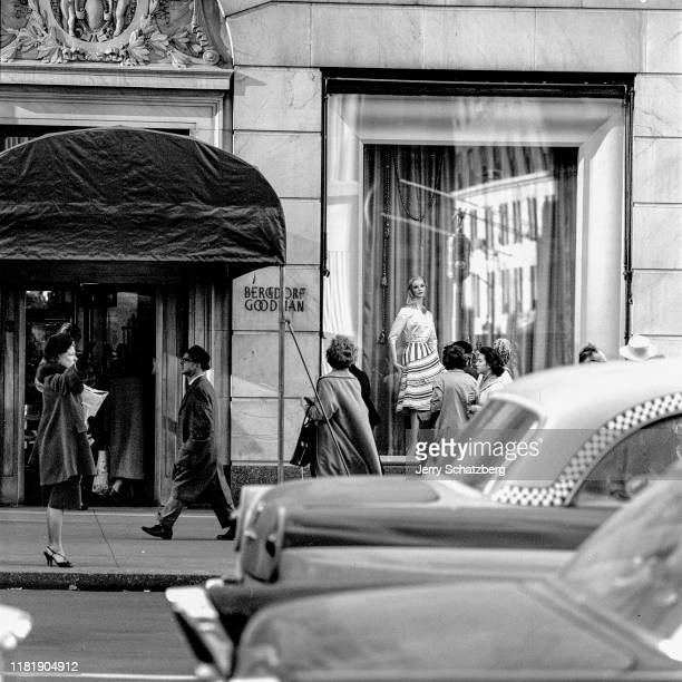 Outside of the Bergdorf Goodman clothing store, a woman in a black fur hat and fur-trimmed coat hails a taxi as pedestrians walk past and window...