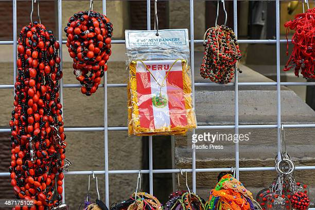 Outside the Chuch of the Holly Innocents a street vendor sells prayer beads and Peruvian flag banners in honor of the processionThe congregation of...