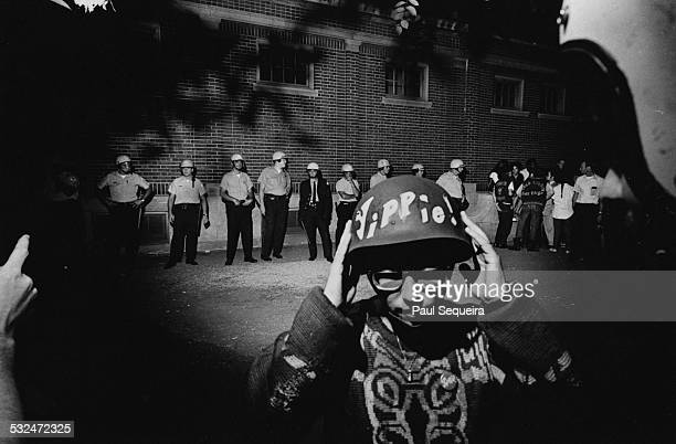 Outside the Lincoln Park fieldhouse during protests at the Democratic National Convention a protestor wears a helmet bearing the handwritten sign of...