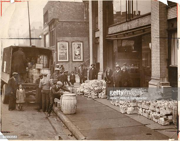 Outside the original Chicago Defender building, newspaper founder Robert Sengstacke Abbott stands amidst bundles of donations to be given out as...