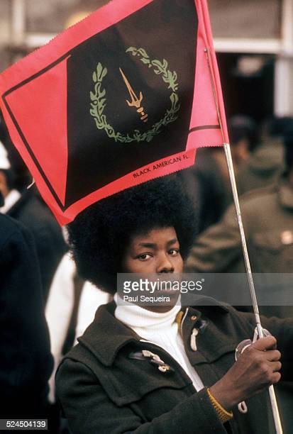 Outside the Rayner Funeral Home a woman holds a flag while waiting to pay last respects to slain Black Panther Party leader Fred Hampton after he was...