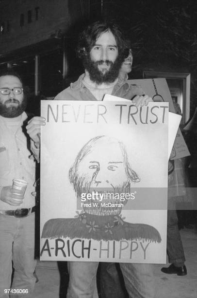Outside the Sotheby ParkeBernet auction of Pop art works an unidentified demonstrator holds up a sign that reads 'Never Trust A Rich Hippy' and...