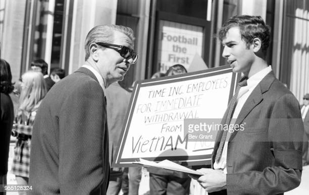 Outside the Time Life Building a man holds a sign that reads 'Time Inc Employees for Immediate Withdrawal from Vietnam Now' in one hand and a...
