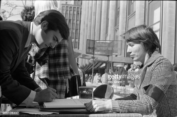 Outside the Time Life Building during the Moratorium to End the War in Vietnam demonstration a man signing a petition at a table staffed by a woman...