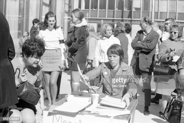 Outside the Time Life Building during the Moratorium to End the War in Vietnam demonstration a woman with a black armband over her blazer sits at a...