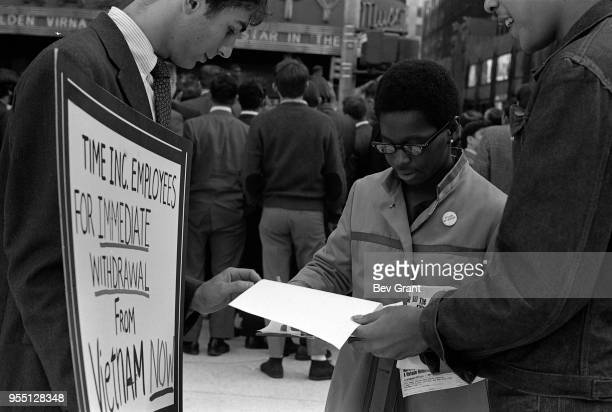 Outside the Time Life Building during the Moratorium to End the War in Vietnam demonstration a woman signs a petition as she stands between two men...