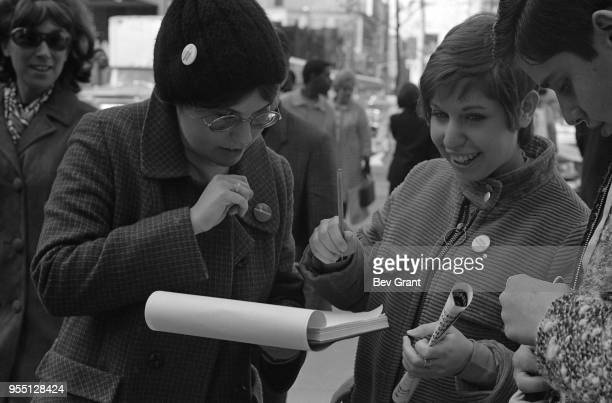 Outside the Time Life Building during the Moratorium to End the War in Vietnam demonstration a woman smiles as she signs a petition New York New York...