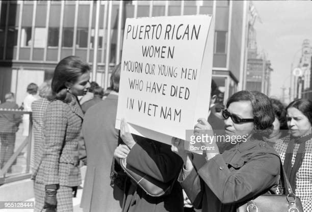 Outside the Time Life Building during the Moratorium to End the War in Vietnam demonstration two women hold a sign that reads 'Puerto Rican Women...