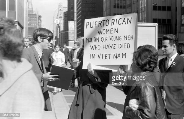 Outside the Time Life Building during the Moratorium to End the War in Vietnam demonstration a man with a petition talks to a pair of women who hold...
