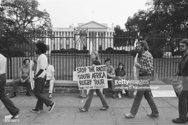 Outside the White House, an anti-apartheid demonstrator carries a placard protesting against the US tour by South African rugby team, the Springboks,...