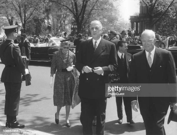 Outside the White House French President Charles de Gaulle walks with US President Dwight Eisenhower while in the United States on a state visit...