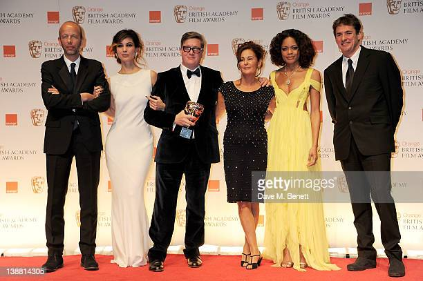 Outstanding British Film winners Tomas Alfredson Tim Bevan Eric Fellner and Robyn Slovo pose with presenters Berenice Marlohe and Naomie Harris in...