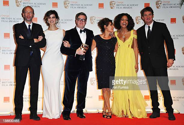 Outstanding British Film winners Tomas Alfredson Tim Bevan Eric Fellner and Robyn Slovo pose with presenters Berenice Marlohe and Naomie Harris...