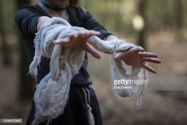 outstreched arms of a child dressed as a zombie in a forest - naughty halloween stock photos and pictures
