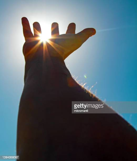 outstretched hand towards the sun wanting to touch it - positive emotion stock pictures, royalty-free photos & images
