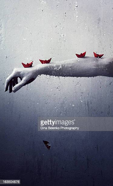 Outstretched hand with red origami  boats