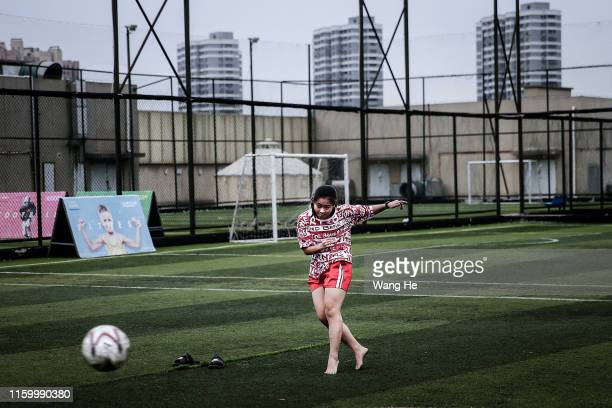 Ouyang Nianchi 22. She is playing football barefoot at starry sky stadium on June 16 .2019 in WuhanHubei Province.China. She comes from Dawu. It's...