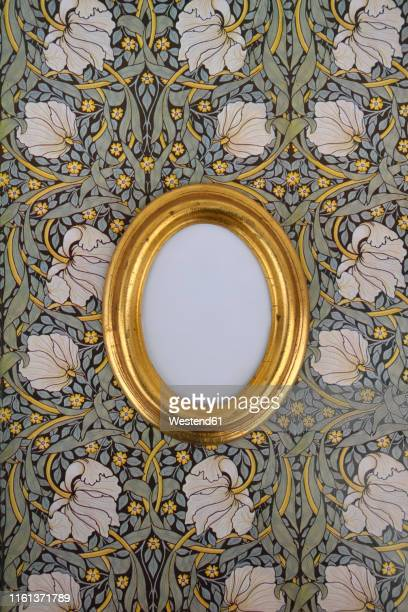 oval golden picture frame on wallpaper with art nouveau floral design - art nouveau stock pictures, royalty-free photos & images
