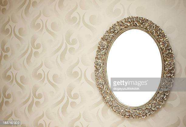 Oval mirror with vintage clipping path style frame on wall