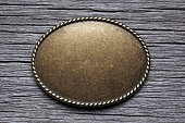 Oval Silver Buckle On Weathered Wood Surface