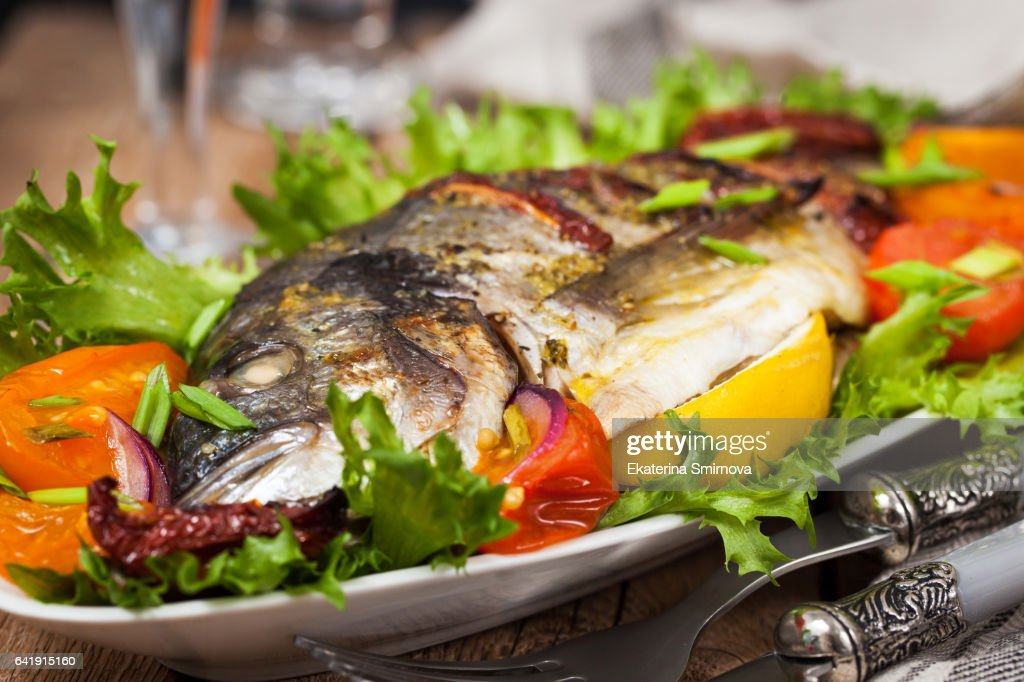 Oven baked whole sea bream fish : Stock Photo