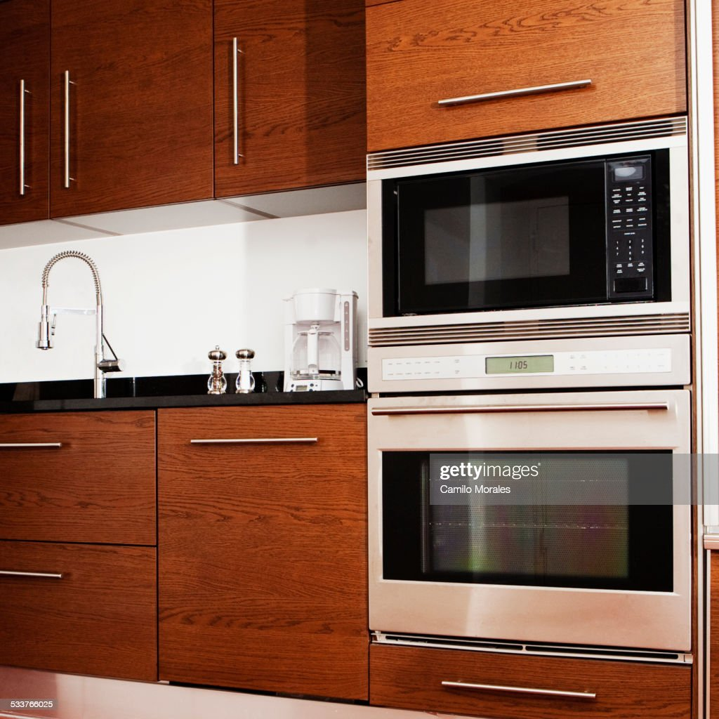 Oven, microwave, cabinets and sink in modern kitchen : Foto stock