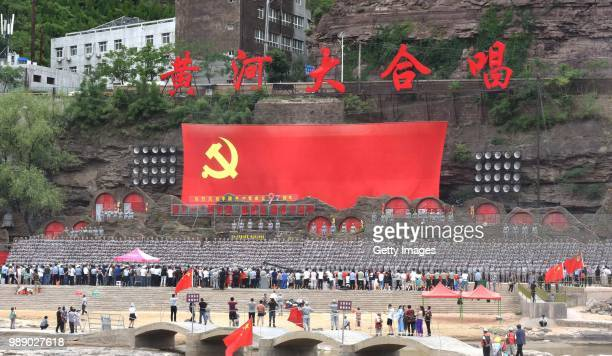 Over 1,000 Chinese cadres and workers sing the 'Yellow River Cantata' to mark the 97th anniversary of the founding of the Communist Party of China by...