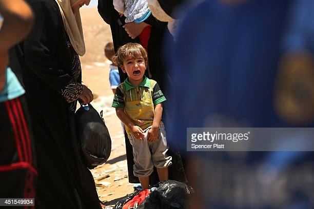 Over 1000 Iraqis who have fled fighting in and around the city of Mosul and Tal Afar wait at a Kurdish checkpoint in the hopes of entering a...