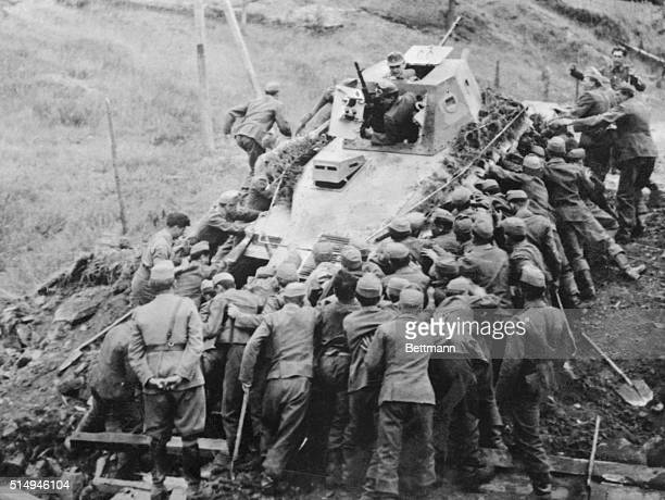 Over 50 Hungarian soldiers are putting their shoulders to the tractor wheels in an effort to recover this disabled Russian tank It was captured by...
