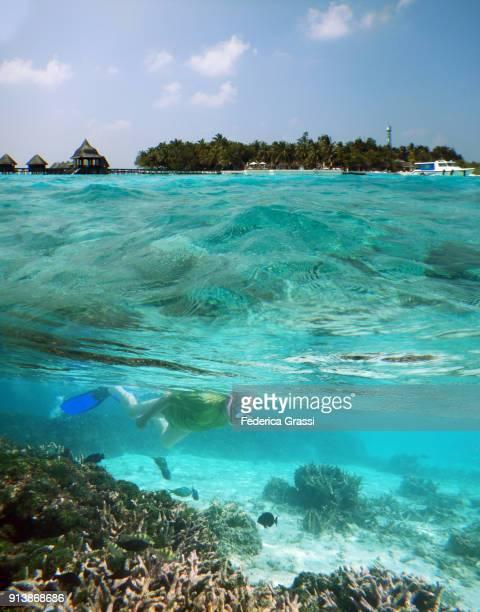 Over And Underwater Maldivian Lagoon With Senior Man Swimming