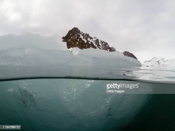 over and underwater view of iceberg, burgerbukta, spitsbergen, svalbard, norway - undersea stock pictures, royalty-free photos & images